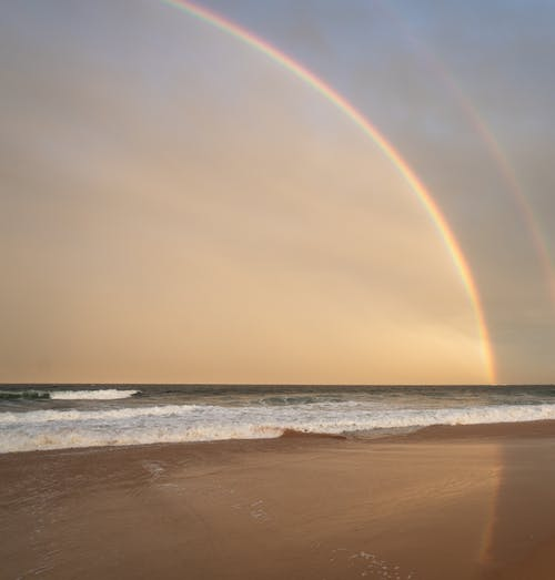 Picturesque scenery of bright rainbow on cloudless sky over waving sea washing sandy coast in nature in tropical country in summer