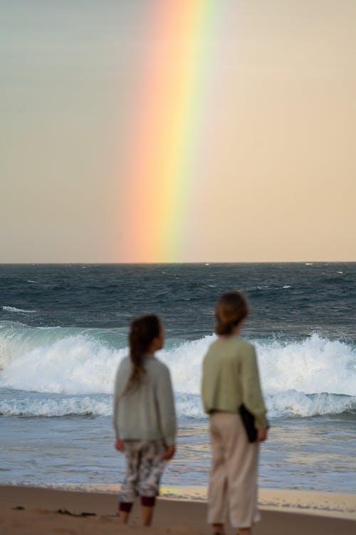 2名穿白色長袖襯衫站在海邊的女人