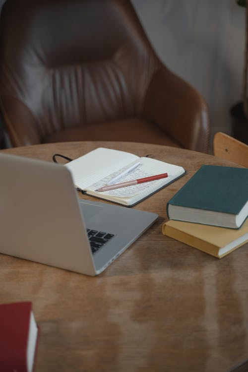 Close-Up Shot of Notebooks beside a Laptop on a Wooden Table