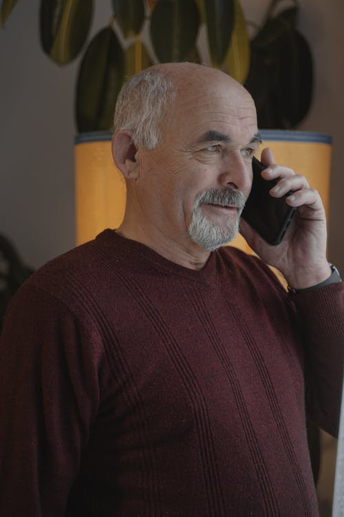 Close-Up Shot of an Elderly Man in Maroon Long Sleeves Having a Phone Call