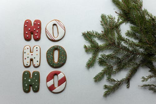 From above of Christmas composition with gingerbread cookies with Ho Ho Ho letters and fir tree branch on white table