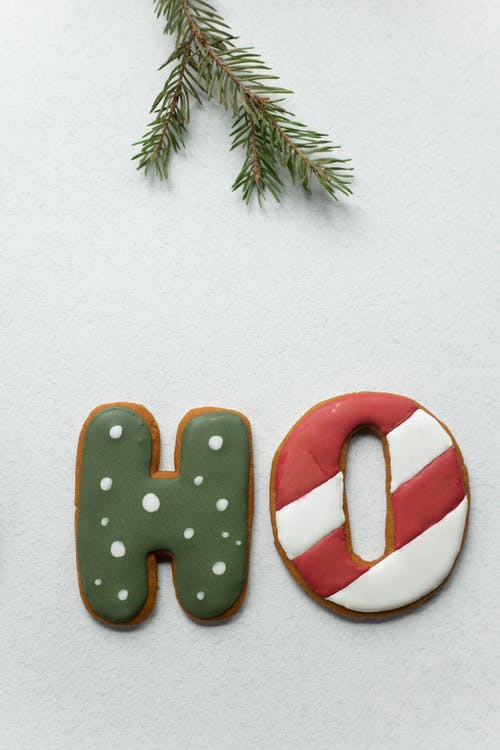 From above of Ho letters gingerbread cookies decorated with royal icing placed on white table near twig of Christmas tree