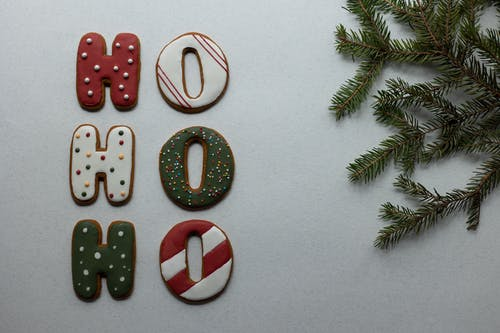 Traditional Christmas gingerbread letters arranged with fir twig on white surface