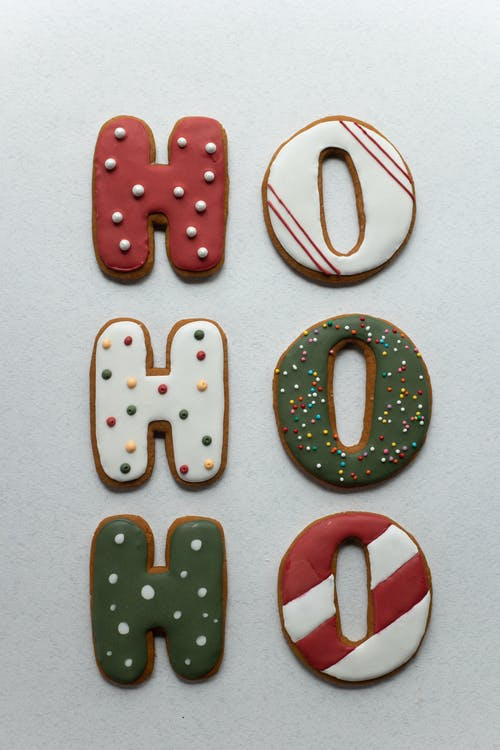 Traditional Christmas yummy gingerbread cookies in form of Ho Ho Ho letters decorated with icing and sprinkles and placed on white background
