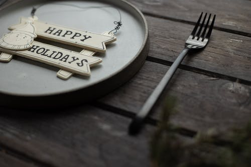 Closeup of Happy Holidays inscription with decorative snowman on plate near fork on wooden table during festive event