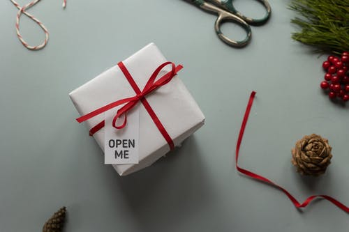 Top view of present box with Open Me inscription on tag and ribbon bow near pine cones on light background