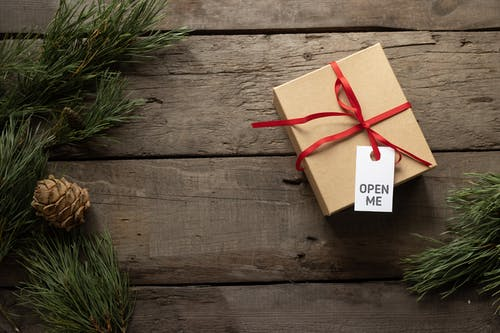 Top view of present cardboard box with ribbon and Open Me title on tag near spruce sprigs on wooden surface during New Year holiday