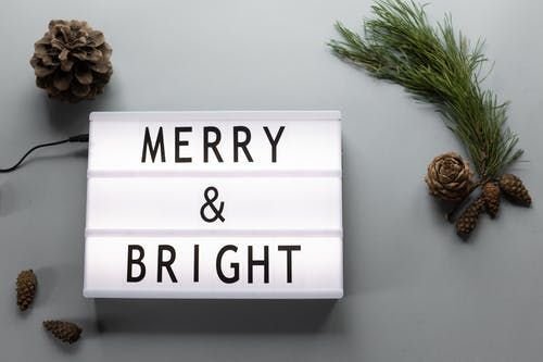 Top view composition of dim lamp with inscription Merry and Bright placed on table near pine cones and coniferous tree branch
