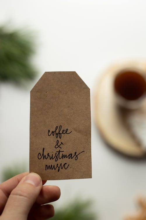 Top view crop person showing craft paper tag with inscription Coffee and Christmas Music above blurred white table during festive season
