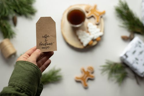 Selective focus of male hand holding brown paper tag with sign Coffee And Christmas Music and Christmas composition on background