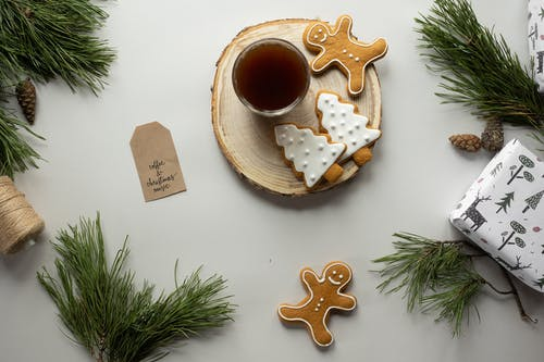 Christmas composition of cookies glass of beverage fir tree branches and wrapped box with present on white background