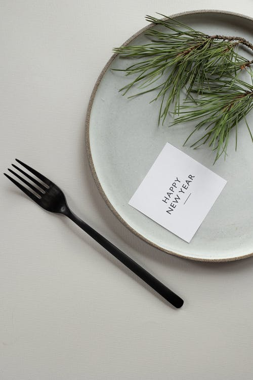 Top view composition of round plate with green coniferous twig and Happy New Year inscription on tag placed on white background near black fork
