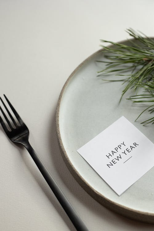 From above of round table with green spruce branch and Happy New Year inscription on card placed on white background with black fork