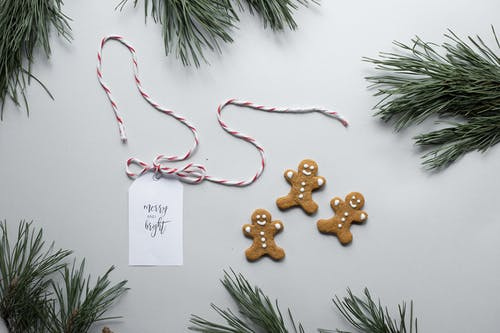 Overhead Christmas composition of gingerbread man cookies placed near gift card with inscription Merry And Bright on white background with green pine tree branches