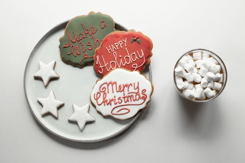 Marshmallows in hot chocolate near various Christmas cookies