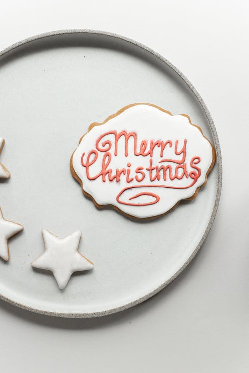 Handmade gingerbread cookie with wish Merry Christmas placed near star shaped cookies