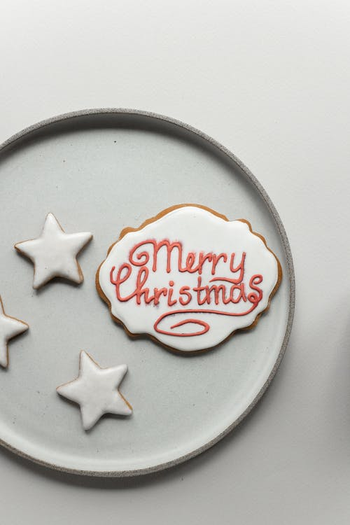From above composition of gingerbread cookie with Merry Christmas wish inscription and small star shaped cookies placed on white ceramic plate