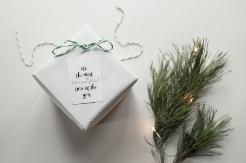 Top view arrangement of wrapped gift box with Its The Most Beautiful Time Of The Year on tag placed on white background near green spruce branches