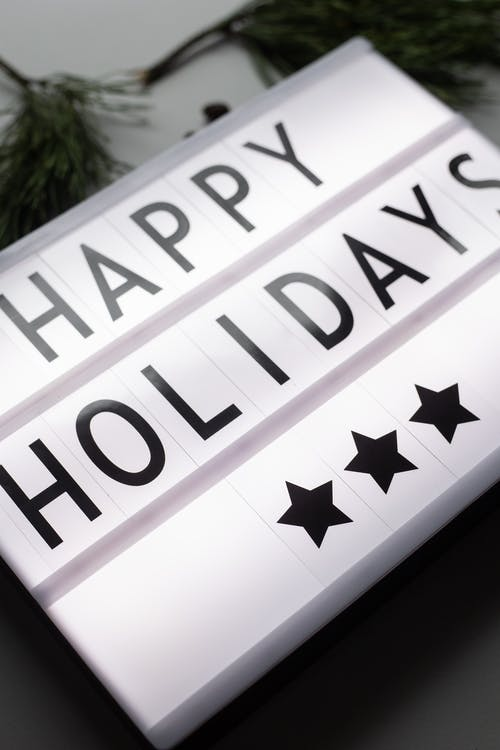 From above of glowing Happy Holidays inscription on white illuminated signboard with stars placed on table with green coniferous branches