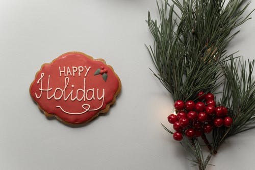 Flat lay composition of gingerbread cookie with red frosting and Happy Holiday inscription placed on gray background with green spruce branch with decorative berries