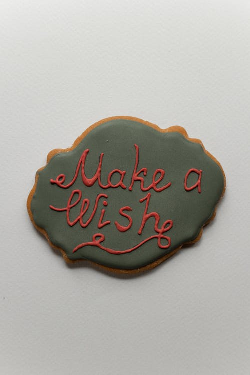 Top view of Make A Wish lettering on green icing of gingerbread baked cookie placed on gray background during Christmas holiday