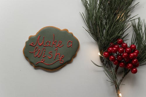 Holiday inscription on cookie and spruce branch