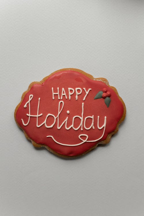 Top view of white Happy Holiday inscription on red icing of gingerbread cookie placed on gray background during Christmas celebration