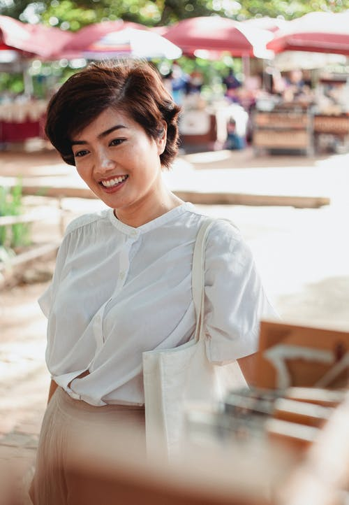 Attractive Asian woman standing on sunny market