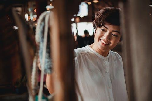 Crop smiling Asian woman choosing gift in souvenir market