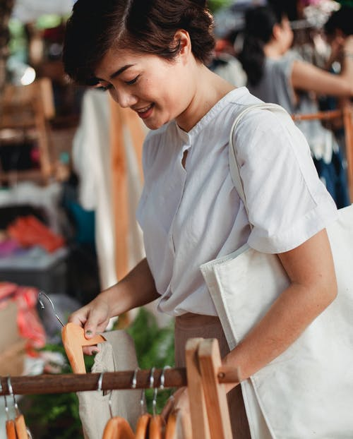 Crop smiling Asian female in trendy white blouse standing near rack with various clothes and choosing outfit in street market