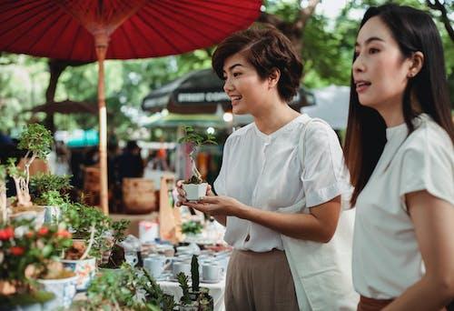 Charming Asian women choosing houseplants in street market