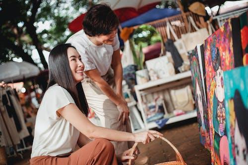 Happy Asian women enjoying colorful drawings in street market