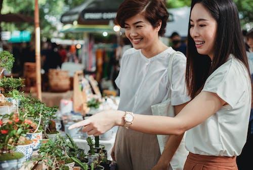 Crop happy Asian women choosing houseplants in market