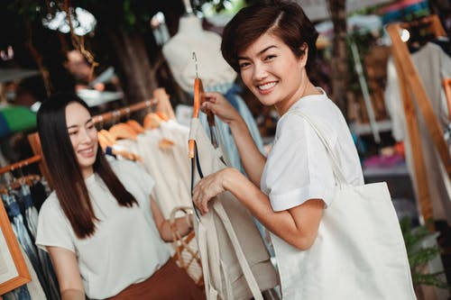 Happy Asian females in stylish summer outfits choosing clothes while standing in sunny street market