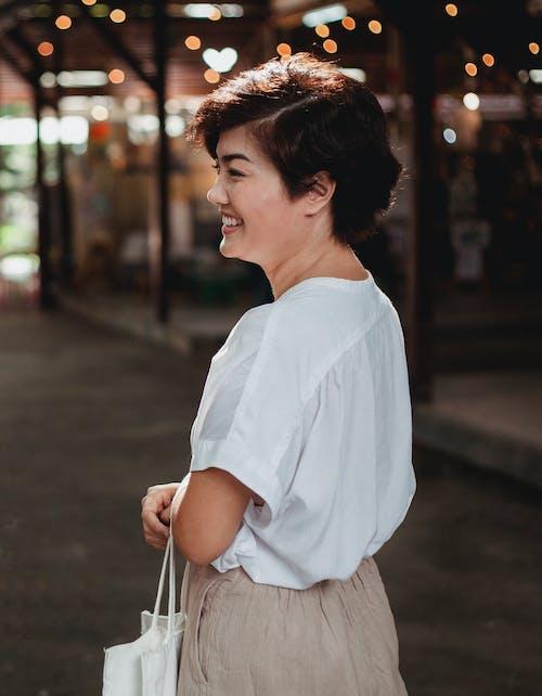 Happy Asian woman walking on street