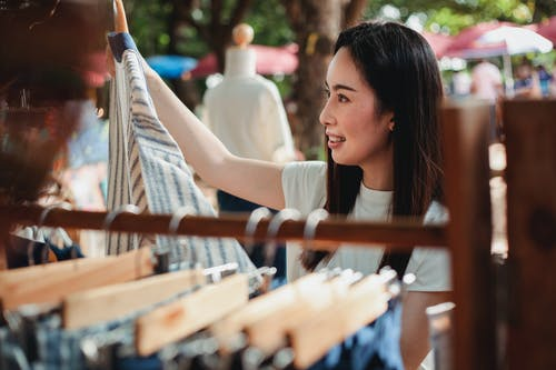 Young Asian woman choosing clothes in street market