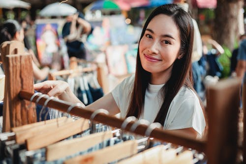 Beautiful Asian woman standing near rack with clothes in market