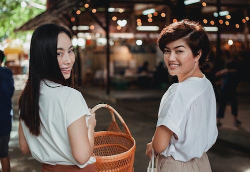 Attractive Asian women walking with wicker basket on pedestrian street