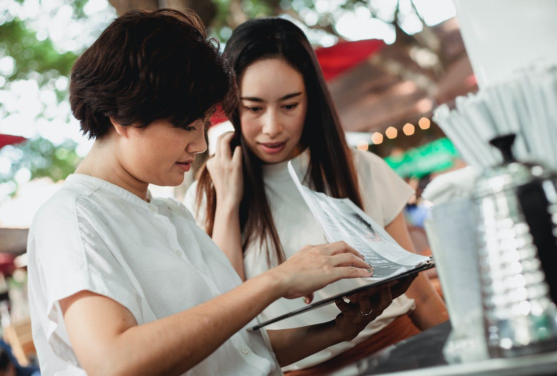 Positive Asian women reading menu in street cafeteria