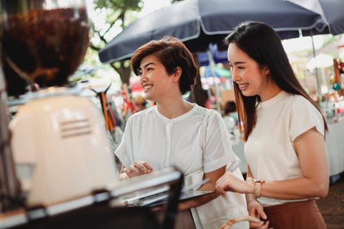 Beautiful smiling ethnic females wearing stylish summer clothes standing near street cafe counter and ordering drink while spending sunny day in outdoors market together
