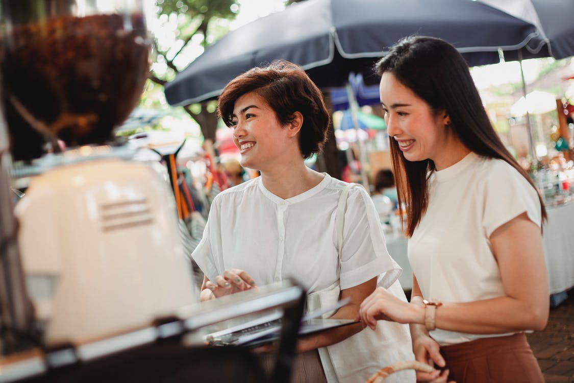 Cheerful Asian women ordering drinks in street cafeteria