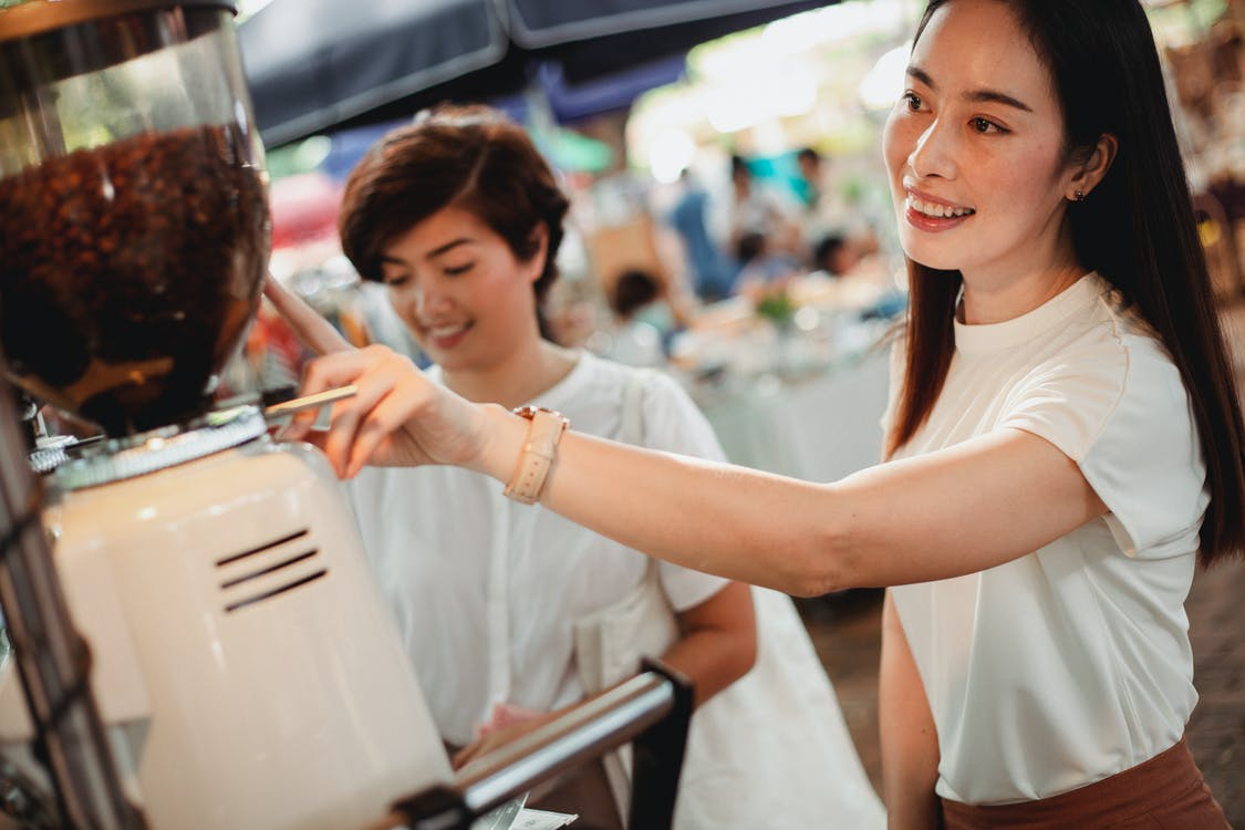 Attractive Asian women ordering coffee in street cafe