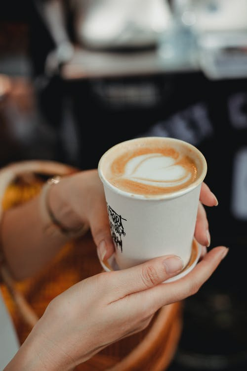 Crop faceless woman holding takeaway cup of aromatic cappuccino
