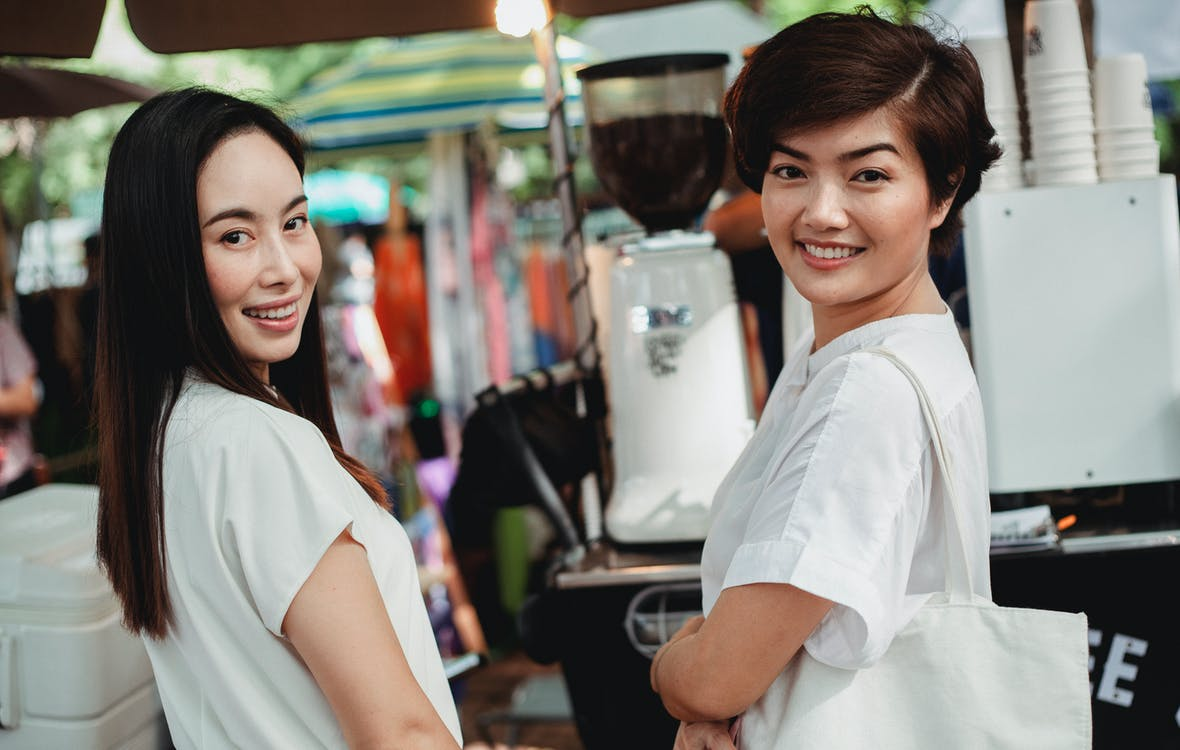 Smiling Asian women standing near street cafeteria counter