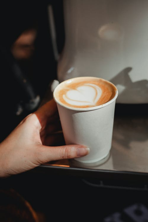 Crop faceless woman touching cup of fresh cappuccino