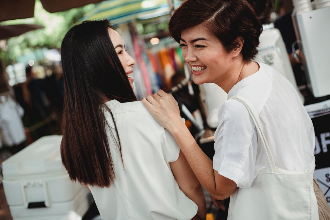 Joyful Asian women laughing while ordering drink in outdoor cafe