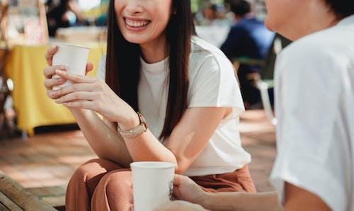 Crop joyful women drinking coffee on sunny street