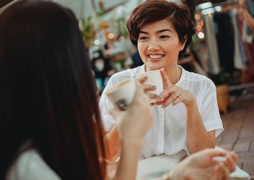 Positive Asian women chatting and enjoying hot drinks on street