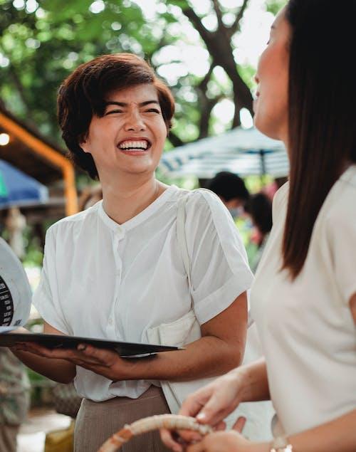 Laughing Asian women standing in street market