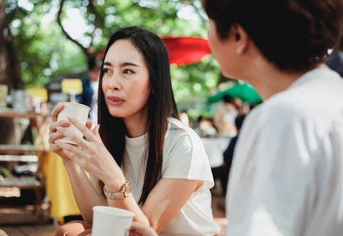 Content young Asian females wearing casual white shirts enjoying fresh aromatic coffee in outdoor cafe and discussing plans